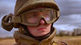 Cara enérgica seria en el casco del soldado caucásico todavía que se coloca y que mira alrededor, siendo aislado en campo de trig almacen de metraje de vídeo