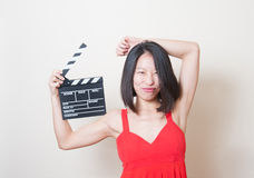 Cara engraçada do vestido vermelho asiático novo da mulher com clapperboard fotos de stock
