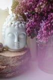 A cara espiritual da meditação do zen da Buda com o lilás violeta bonito do ramo floresce Decoração home, ainda conceito da vida Imagem de Stock Royalty Free