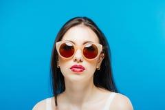 Cara fêmea com os óculos de sol perfeitos limpos da pele e da forma no fundo azul imagem de stock