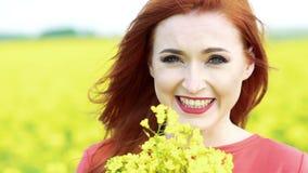 Cara feliz da menina que sorri na câmera com o ramalhete da flor da violação Movimento lento filme
