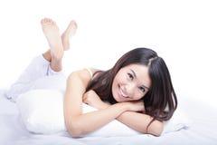 Cara feliz de la sonrisa de la mujer mientras que miente en la cama Imágenes de archivo libres de regalías