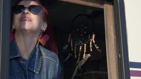 Cara feliz de las mujeres jovenes del estilo del indie que mirando al exterior del pelo del soplo del viento de la ventana metrajes