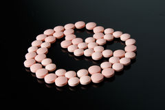 Cara feliz de las píldoras rosadas en negro Foto de archivo libre de regalías