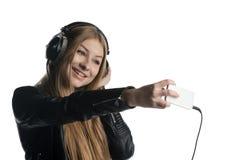 Cara feliz de una muchacha en los auriculares atados con alambre que hacen una mueca Imágenes de archivo libres de regalías