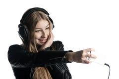 Cara feliz de una muchacha en los auriculares atados con alambre que hacen una mueca Imagenes de archivo