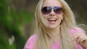 Cara feliz del baile rubio hermoso y de la sonrisa de la señora en el partido al aire libre metrajes