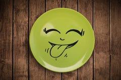 Cara feliz dos desenhos animados do smiley na placa colorida do prato Foto de Stock Royalty Free