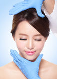 Cara femenina hermosa con el guante de la cirugía plástica imagen de archivo