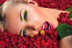 Cara femenina hermosa en frambuesas fotografía de archivo libre de regalías