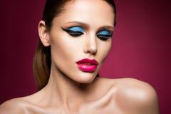 Cara femenina joven hermosa con maquillaje multicolor de la moda brillante Fotos de archivo