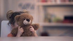 Cara femenina triste de la cubierta del niño por el juguete del oso de peluche, problema de la familia, abuso de la soledad metrajes