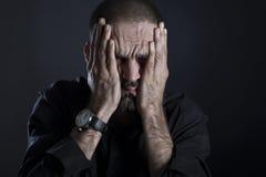 Cara frustrante cansado da coberta do homem com mãos Fotografia de Stock