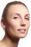 Cara hermosa de la mujer joven con crema cosmética en una mejilla Concepto del cuidado de piel Retrato del primer aislado en blan imagenes de archivo