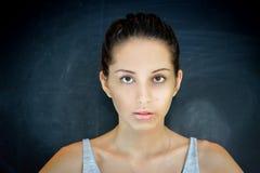 Cara hermosa de la mujer joven con la piel fresca limpia en fondo de la pizarra fotografía de archivo