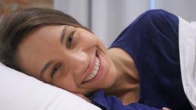 Cara hispánica sonriente de la mujer que miente en la cama, opinión cercana de la cámara metrajes