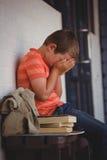 Cara infeliz de la cubierta del muchacho con las manos mientras que se sienta en banco Fotos de archivo