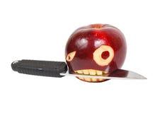A cara irritada é cinzelada em uma maçã e em uma faca fotos de stock royalty free