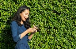 Cara linda de la sonrisa de la muchacha asiática con el teléfono móvil en parque verde Fotografía de archivo