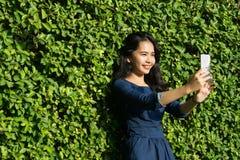 Cara linda de la sonrisa de la muchacha asiática con el teléfono móvil en parque verde Imagen de archivo libre de regalías