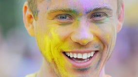 Cara masculina joven en el polvo del color que sonríe cerca para arriba, divirtiéndose en el festival de Holi metrajes