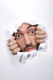 Cara masculina a través del agujero Fotos de archivo libres de regalías