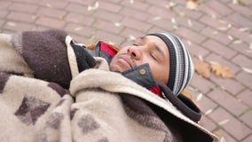 Cara miserável do homem desabrigado que dorme no banco, sentindo frio e infeliz video estoque