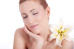 Cara natural hermosa de la mujer con la flor aislada imagen de archivo