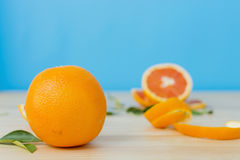 Cara orange on wooden table over blue background. Royalty Free Stock Photo