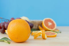 Cara orange on wooden table over blue background. Stock Image
