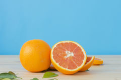 Cara orange on wooden table over blue background. Stock Photo