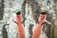 Cara pintada nos dedos estudantes que guardam seu diploma após a graduação Fotos de Stock