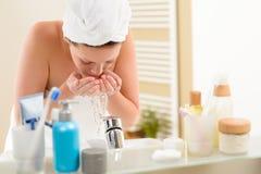 Cara que se lava de la mujer sobre fregadero del cuarto de baño fotografía de archivo libre de regalías