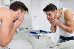 Cara que se lava del hombre en cuarto de baño Imagen de archivo libre de regalías