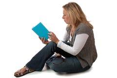 Cara rubia de la mujer en sentarse y la lectura Imágenes de archivo libres de regalías