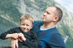 Cara satisfecha de un hijo en abrazo cómodo de un padre Imagenes de archivo
