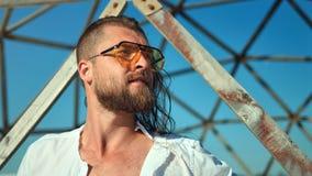 Cara segura do close-up dos óculos de sol vestindo do homem farpado da forma que levantam no fundo da grade vídeos de arquivo