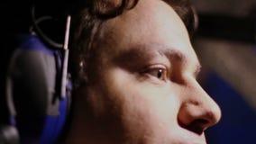 Cara seria del piloto durante vuelo, crewmember plano que mira el panel de la carlinga almacen de metraje de vídeo