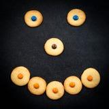 Cara sonriente de galletas infantiles en fondo negro Imagen de archivo libre de regalías