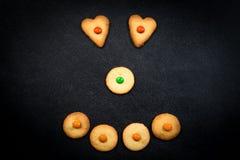 Cara sonriente de galletas infantiles en fondo negro Imagen de archivo