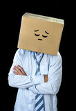 Cara sonriente de la historieta del hombre de negocios que lleva triste y deprimido pintada en la caja de cartón sobre su cabeza Imagenes de archivo