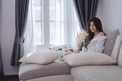 Cara sonriente de la mujer asiática joven hermosa en la sentada blanca de la camisa Imágenes de archivo libres de regalías