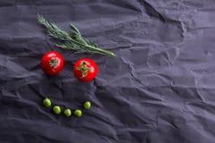 Cara sonriente de verduras en fondo de papel negro foto de archivo