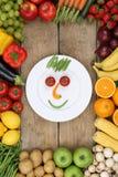 Cara sonriente de verduras y de frutas en la placa con los tomates a Imágenes de archivo libres de regalías