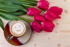 Cara sonriente del café con los tulipanes rojos en la madera Visión superior Imagenes de archivo