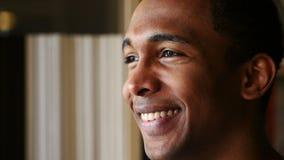 Cara sonriente del hombre afroamericano joven, cierre de la vista lateral para arriba almacen de video