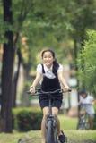 Cara sonriente dentuda de la bicicleta asiática del montar a caballo del adolescente en el PA verde Imagen de archivo libre de regalías