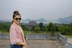 Cara sonriente dentuda de la mujer asiática que se coloca en ninh del templo del dinh del bai Fotos de archivo