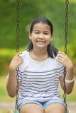 Cara sonriente dentuda del adolescente asiático y el sentarse en el oscilación en verde Imagen de archivo libre de regalías