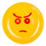 Cara sonriente enojada hecha en la placa Imágenes de archivo libres de regalías